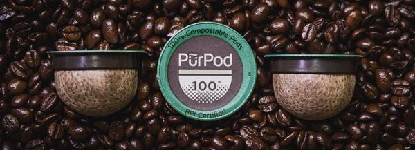 Image of Pur Pod single serve compostable placed on coffee beans